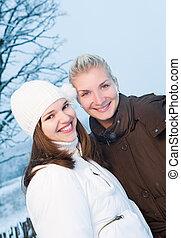 Two beautiful women in winter clothing outdoors