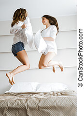 Two beautiful women jumping from joy on bed and fighting with pillows