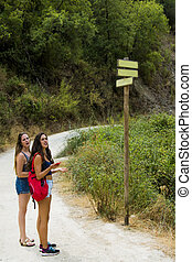 Two beautiful women on a pole with blank road signs in nature on a mountain road