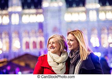 Two beautiful women on a walk in illuminated night city.