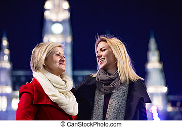 Two beautiful women on a walk in illuminated night city.