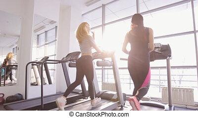 Two beautiful women run on treadmill in gym.