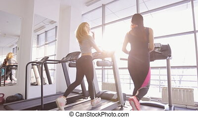 Two beautiful women run on treadmill in gym.