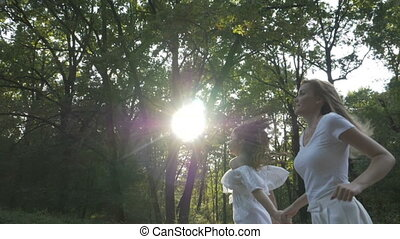 Two beautiful women running happily in nature with trees and...