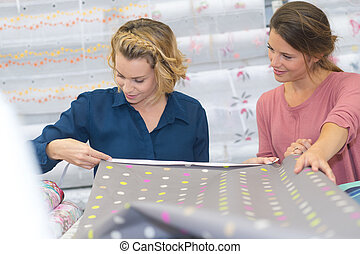 two beautiful women selecting tissue at the fabric shop
