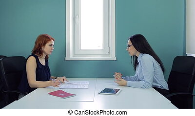 Two beautiful women sign contract at office.