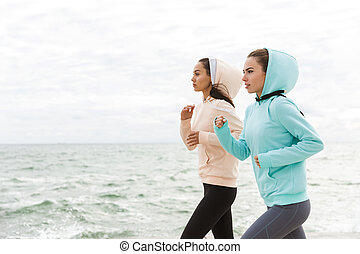 Two beautiful young fitness women jogging outdoors