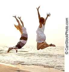 Two beautiful young girlfriends jumping on the beach at ...