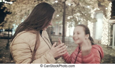 Two beautiful young girls are dancing on a city street at night. Mom and daughter dance listening to music in headphones.