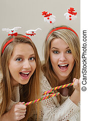 two beautiful young girls enjoying and having fun with Christmas sweet candys