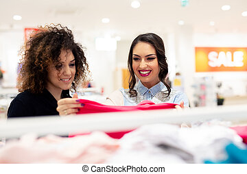 Two beautiful young girls shopping trendy kid clothes