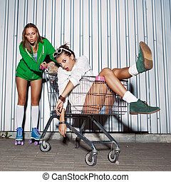 two beautiful young girls with a skateboard, roller scates and a