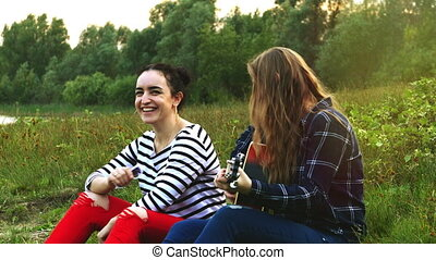 Two beautiful young hipster girls, rejoice and sing to guitar songs. 4K