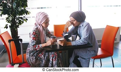 Two beautiful young Muslim women in a airport cafe...