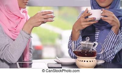 Two Beautiful Young Muslim Women in Cafe Communicate