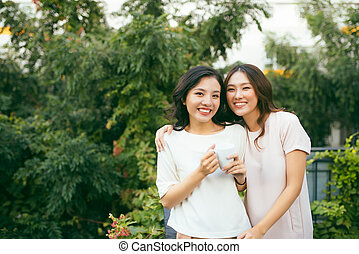 Two beautiful young well-dressed women chatting outdoors over coffee