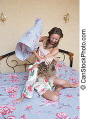 Two beautiful young woman fighting with pillows