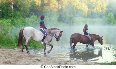Two beautiful young woman with their horses swimming in the...