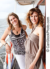 Two beautiful young women a Caucasians standing together on the deck of yacht in cruise