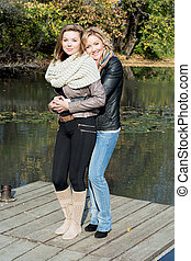 Two beautiful young women and pond in the autumn park