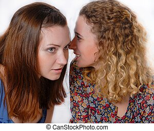 Two beautiful young women chatting sicrets on white background