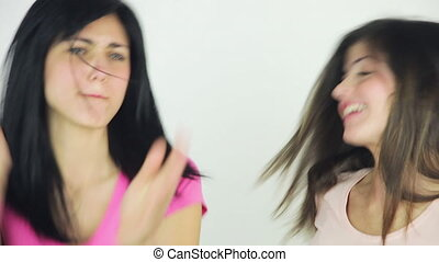Two beautiful young women dancing isolated