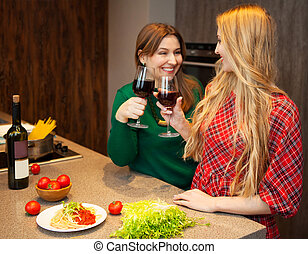Two beautiful young women friends drinking red wine together