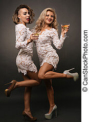 two beautiful young women girlfriends in white short dress dance with martini glasses