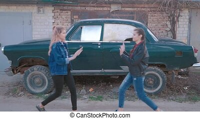 Two beautiful young women giving high five - Pretty girls on a old retro car background having fun - Best girlfriends making a promise
