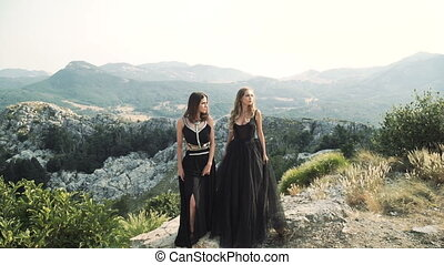 two beautiful young women in posh black dresses posing together on camera against the background of a mountain landscape.