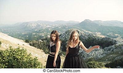 two beautiful young women in posh black dresses posing...