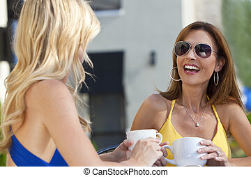 Two Beautiful Young Women Laughing and Drinking Coffee