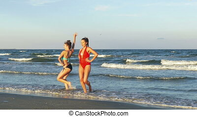Two beautiful young women playing on the beach and dancing