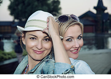 Two beautiful young women posing in front of camera