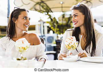 Two beautiful young women smiling and having a fruit salad in a restaraunt