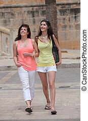 Two beautiful young women strolling in town