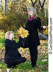 Two beautiful young women with autumn leaves in park