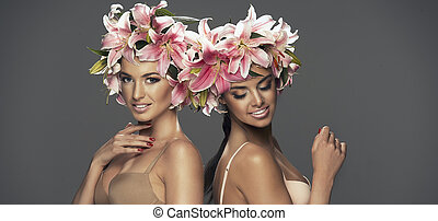 Two beauty smiling girls with flowers in hair