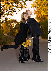Two beauty young blondes with autumn leaves on a road