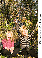 Two beauty young women in autumn park