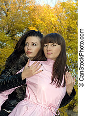 Two beauty young women outdoors in the autumn