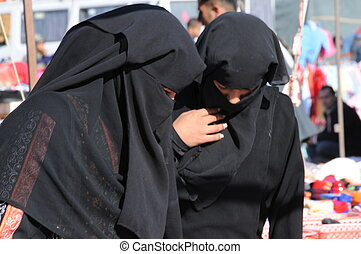 two bedouin women in traditional dress at souk