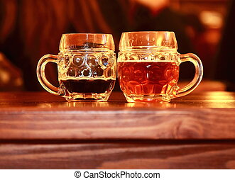 Two beer glasses on wooden table in bar. Dark and lager tasty beer