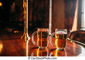 Two beer mugs on wooden bar counter, nobody - Two beer mugs ...