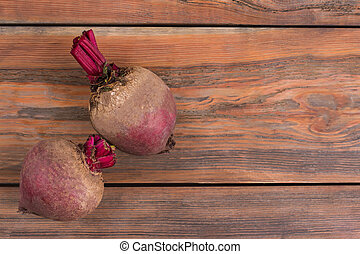 Two beetroots on wood.