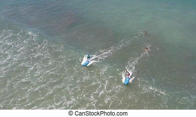 Two Beginners Surfing In Ocean Surf School. People surfing...