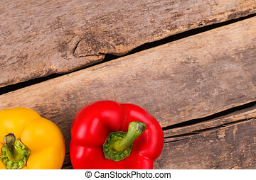 Two bell peppers on wood and copyspace.