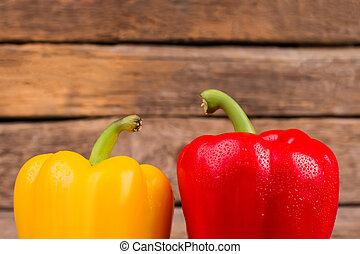 Two bell peppers on wooden background.