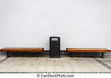 Two benches by a wall