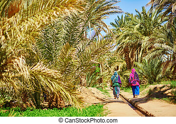 Two berber women in national clothes walking in oasis of Merzouga village in Sahara desert, Morocco